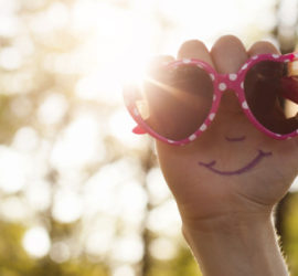 Happy face and sunglasses on a hand